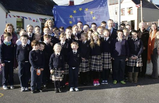 MEP Seán Kelly with Knocknagoshel PP Fr. Eoin Mangan; Scoil Mhuire NS principal, Máire Collins, teachers and pupils at the raising of the European flag at the school.