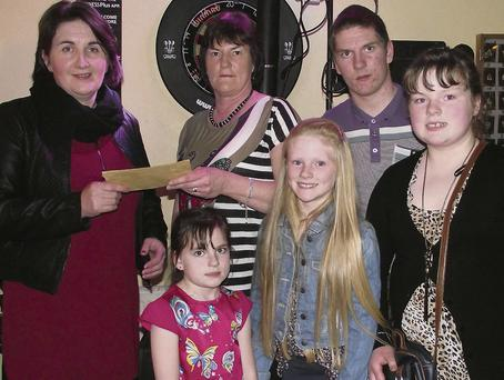 Geraldine O'Donoghue (left) accepts a cheque from Mary and the Fitzmaurice family, Paudie, Laura, Ava and Sharon on behalf of Glebe Lodge, Castleisland at the presentation of the Paudie Fitzmaurice Memorial Tractor Run proceeds at the Half Barell Bar on Saturday night. Photographs courtesy of: Nora Fealey.