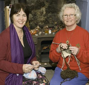 Fidelma Walsh, crocheting and Maureen Connolly, knitting in front of the Stanley range at Craftshop Na Méar.