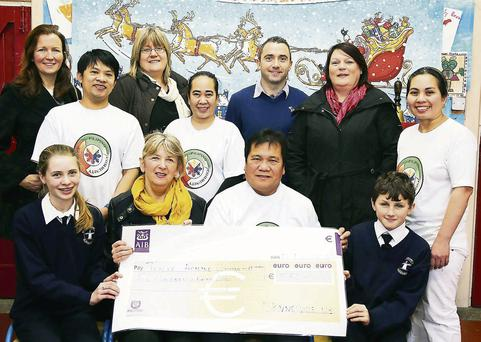 Members of the Parents Council at St. Brendan's Primary School, Blennerville presenting a cheque for €550 to Noel Sebbey to help typhoon victims in the Philippines. Front, from left: Sheanna Marie Murphy, Mary Wallis, Noel Sebbey and Darragh O'Connor. Back, from left: Armond Perez, Siobhan Corridan, Rose Aday, Principal Terry O'Sullivan, Maura O'Donnell.