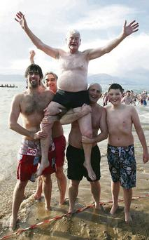 P.J. Costello, Tralee, celebrating his 60th Christmas day swim at Fenit last year, helped by Pat and Stephen Costello, Brendan and Daire Kennelly, Tralee.
