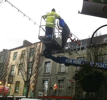 Workers brave the weather to ensure Tralee's festive lights are safe.