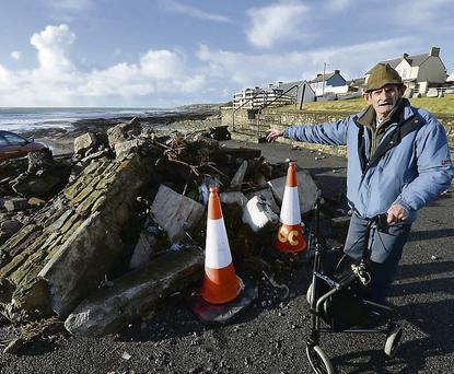Part of Ballyheigue Beach car park was covered in Stones, sand and seaweed after a wall was knocked down by the sea . Robert Kelly from Ballyheigue stands by the wall .