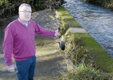 Cllr. Bobby O'Connell points to the area of the Glounsharoon River which breaches the retaining wall on its diverted journey towards Tullig.