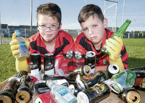 Conor O'Sullivan and Dillon Casey from Ballyheigue GAA Club with just some of the cans and bottles found on their playing field.