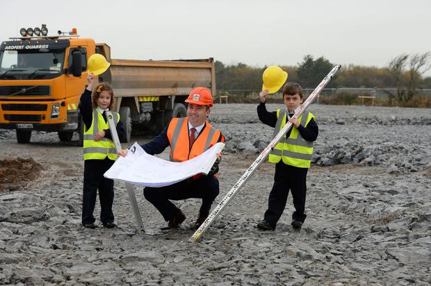 School principal Terry O'Sullivan with the plans and students Caoilainn Culloo and Roary Daly