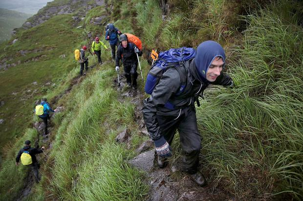 Anil Chalisey leads the Ultimate pilgrims over a pass in the Reeks in the battle against the sodden and windy conditions on Saturday