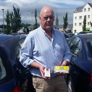 Former Garda Det Chief Super, Kevin Donohoe displaying the 'Illicit Whites' brand 'Gold Mount' counterfeit pouch of 'Amber Leaf'