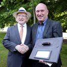 Vincent Kidd presenting a piece of Valentia Cable mounted on Valentia Slate to President Higgins
