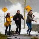Astrid Deursen, Peter Deursen and Brigid Van der Linden race the waves at the Glen Pier, Ballinskelligs, as Storm Ophelia lashed the coast on Monday. Photo by Stephen Kelleghan