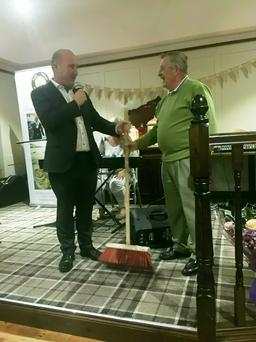 Michael Egan being presented with a road sweeping brush by Vincent Kidd of the Royal Hotel, as a symbol of his Tidy Towns endeavours.