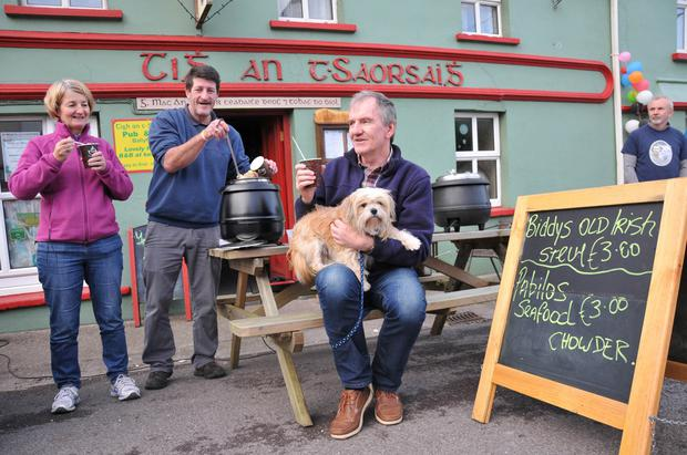 Diarmaid Mac an tSaoir dishing up 'Biddy's Old Irish Stew' to Mary Reilly and Gary Granville, along with Dude the dog.