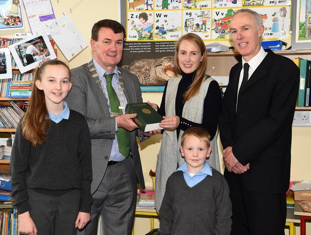 Mayor John Sheahan and County Library Tommy O'Connor presenting the dictionary to Miriam Madigan with pupils Tara Buckley and Ryan Fears at Meentogues National School, Rathmore