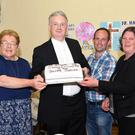 Fr George Hayes cutting the cake at his Silver jubilee celebration with some of the organising committee Helena Murphy, Shane O'Riordan and Mary McCarrick at the Glenflesk Community Centre on Saturday