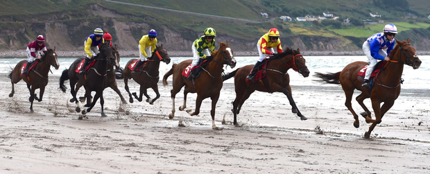 Horses and jockeys battle it out on the water's edge