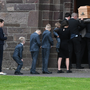 Emma's remains are brought into the church