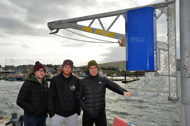 Local fishermen Liam Flannery, Adam Flannery and Tom Brosnan beside the crane that has been installed on the quayside in Dingle, but is not yet available for use