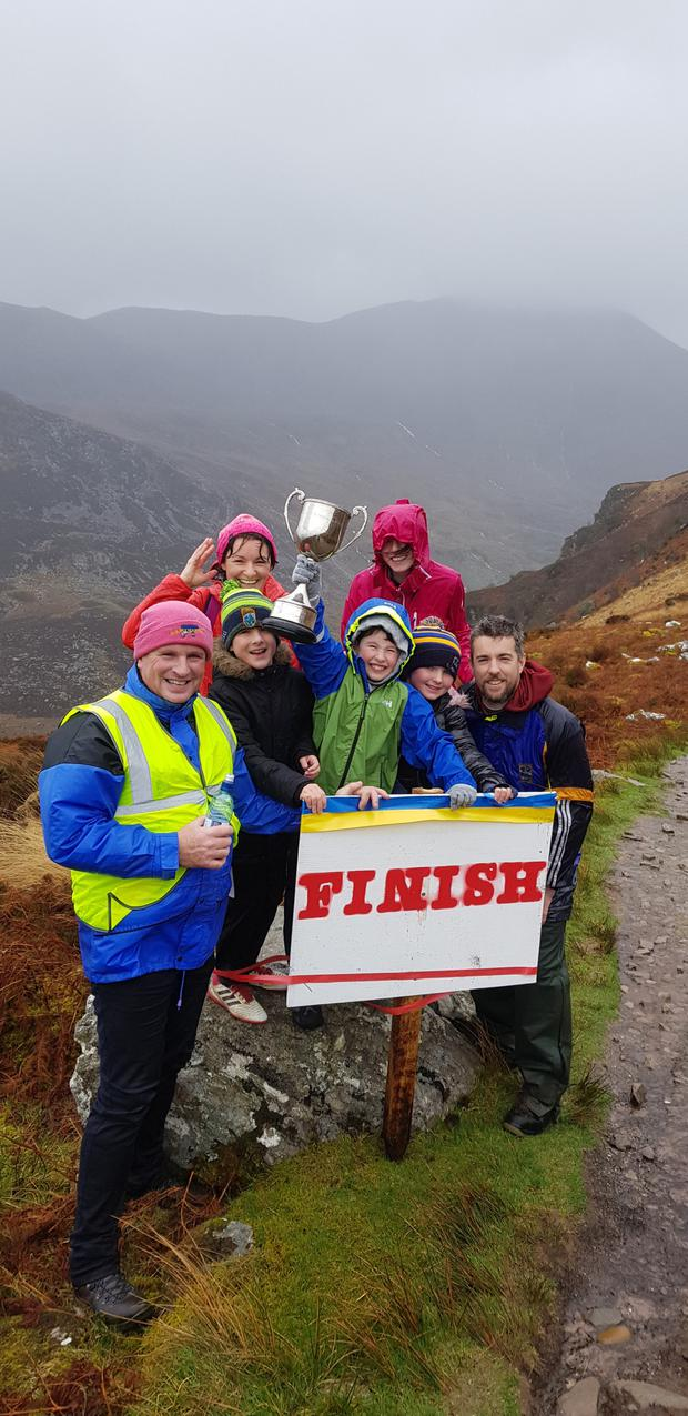 Some of the participants who braved the wind and rain to take part on Saturday's Strickeen Walk, accompanied by the All-Ireland Junior Club Football trophy.