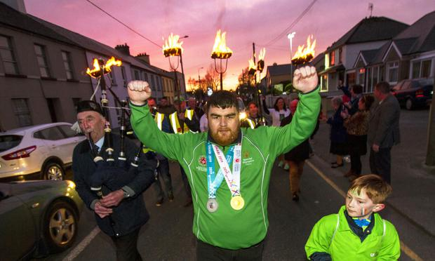 There was a hero's welcome home on Saturday night for Castleisland's Special Olympics World Games gold and silver medallist, Gary O'Sullivan with a torch-lit parade through his home town. Gary is flanked here by his cousin, Jamie Davis and Piper, Noel O'Mahony. Photo by: John Reidy