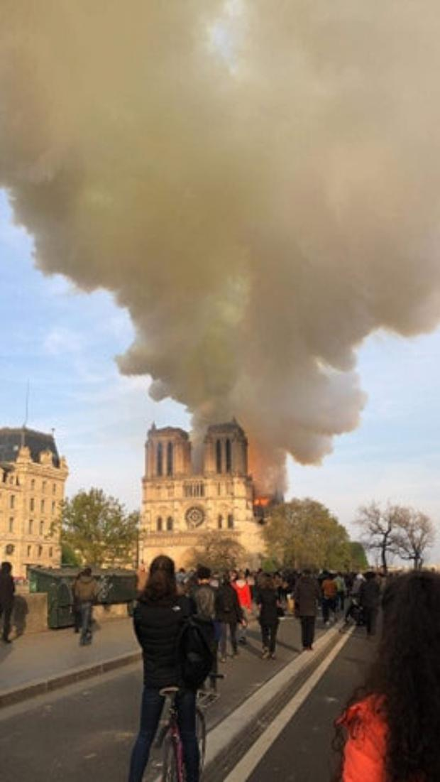 Parisians and tourists watch as the fire engulfs the historic Notre Dame cathedral on Monday evening. Photo by Loretto O' Sullivan