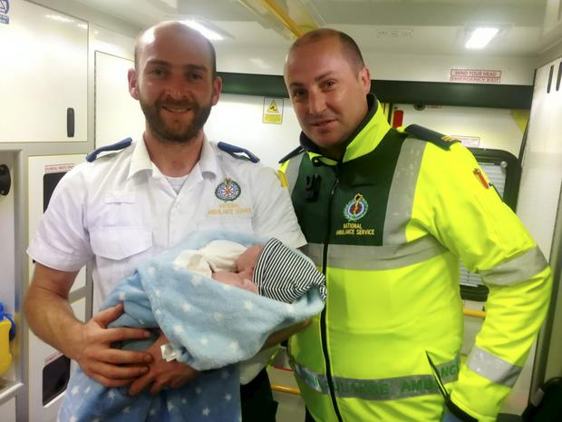 Eugene Cronin (Currow) and Kevin O'Flaherty (Killarney) from Kenmare Ambulance Service with baby Jamie, whom they helped deliver on the side of the road