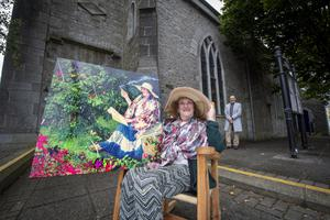 Delia O'Sullivan immortalised at her leisure in her Ballybunion garden by Dave Morrison, pictured behind