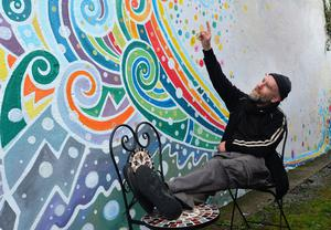 Domhnal Ó Bric with the 'Tonn Fuaime' (sound wave) mural he painted with the help of Eleanor Yates in Pucaí's Lane. Photo by Declan Malone
