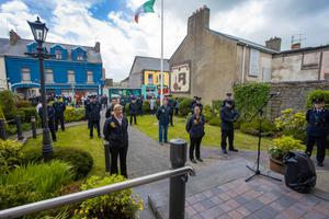 Members of An Garda Síochána observe a minute's silence for slain Gda Colm Horkan at Listowel Garda Station on Sunday, with the tricolour at half mast
