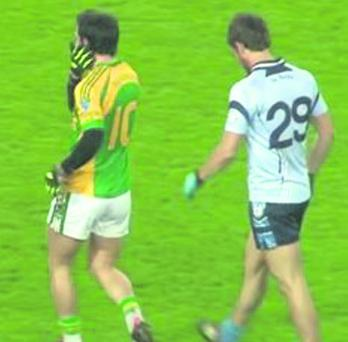 Paul Galvin wipes the side of his face after the incident with a Cookstown player.