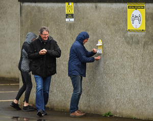 Spectators use hand sanitiser on their arrival into the ground prior to the Kerry County Senior Club Football Championship Group 1 Round 1 match between Kenmare Shamrocks and Kerins O'Rahillys at Fitzgerald Stadium. Photo by Brendan Moran / Sportsfile