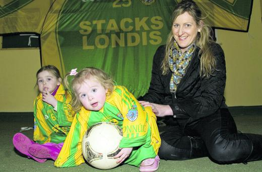 With the enthusiasm of a Finuge defender Baby Isobella McEnery breaks away with the ball from mom, Nollaig and sister, Lucy Kate at the Finuge team press night at the clubhouse on Friday night. Photo: John Reidy
