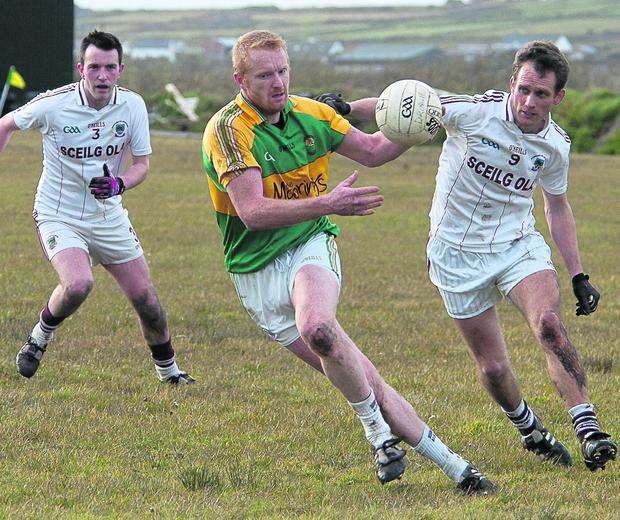 Aidan O'Sullivan of Skellig Rangers turns as he tries to shake off Dominic O Súilleabhain and Colm O'Concubhair of Dromid Pearses in their county intermediate football championship match in Portmagee on Saturday evening. Picture by Stephen Kelleghan