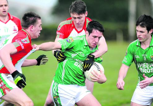 Pa Wren, Milltown/Castlemaine, comes under severe pressure from Damien O'Leary and Kieran Murphy, Kilcummin, in the County Senior Club Football Championship in Milltown on Sunday. Photo by Michelle Cooper Galvin