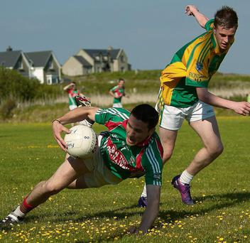 Adrian O'Connell of St Michaels/Foilmore goes to ground while being closely watched by Michael Stackpoole of Finuge.	Photo: Stephen Kelleghan