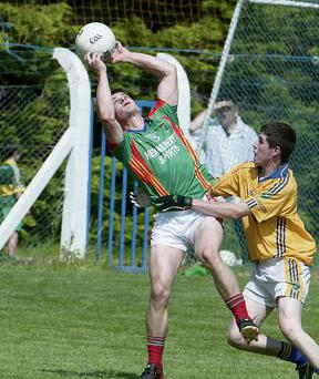 Mid-Kerry's Gavan O'Grady get to the ball before Feale Rangers Sean T. Dillon in the County Senior Football Championship in Ballylongford