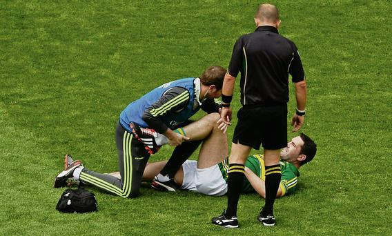 Bryan Sheehan, Kerry, receives medical treatment on the field before being substituted early in the game