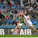 Anthony Maher, Kerry, kicks a point despite the best efforts of Tiernan McCann, Tyrone