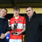New Kerry minor manager Peter Keane of Keanes SuperValu Killorglin presents the Man of the Match award to Dingle team captain Conor Geaney with (right) County Board chairman Patrick O'Sullivan