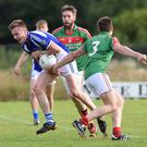 Templenoe's Josh Holland challenged by Damien O'Leary, Kilcummin, in the County Senior Football League in Kilcummin on Saturday. Photo by Michelle Cooper Galvin
