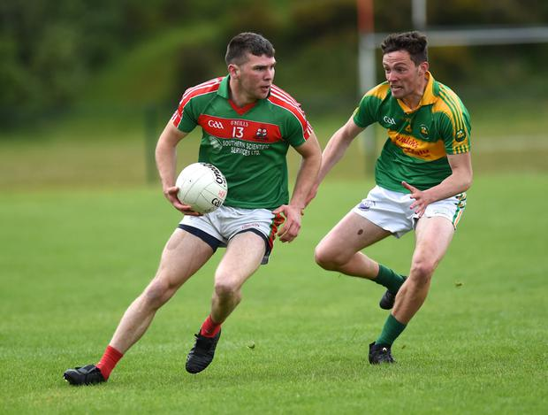 Kevin McCarthy, Kilcummin chased by South Kerry's Fionán Clifford in the Kerry County Garvey Supervalu Senior Football Championship Round 2B at Lewis Road, Killarney on Sunday. Photo by Michelle Cooper Galvin