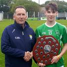 Ger Hussey on behalf of Coistena nÓg presents the trophy to Ballyduff captain Darragh Shanahan after they claimed the Under 16 county title recently