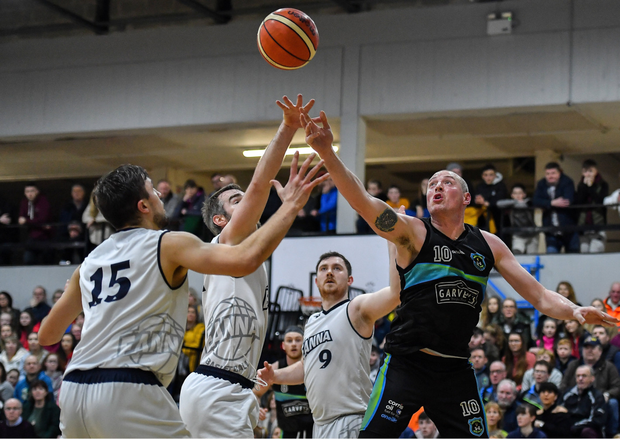 Kieran Donaghy of Garvey's Warriors Tralee in action against DBS Eanna players, from left, Marko Tomic, Mark Ryenolds and Neil Lynch during their Superleague match at Tralee Sports Complex