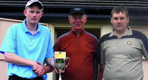n Gerry O'Sullivan, Kerry Pitch and Putt County Board chairman, presents Jonathon Goodall, left, with the winner's cup after the Tralee man won the county senior strokeplay title, with runner-up Damien Fleming pictured alongside.