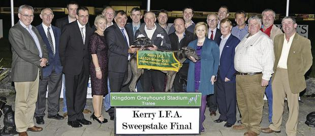 Kerry I.F.A. County Chairman Seàn Brosnan presents the trophy to winning trainer Frank Flavin (Listowel) on behalf of his son and owner Frank Flavin after Sarkozy Scolari won the Kerry I.F.A. Sweepstake Final at the Kingdom Greyhound Stadium on Friday night. Included in the photo Teresa Keane, Declan Dowling, KGS Sales and Operations Manager, and the many Kerry I.F.A. officers and connections to the owner. Photo by Denis Walsh