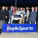 Kerry football team captain Bryan Sheehan presents the winner's trophy to Christine McElligott with joint-owners Mike Davis and Paddy McElligott to the rear after Paradise Maverik won the 2016 Boylesports Race of Champions Final at Kingdom Greyhound Stadium last Friday. Included, from left, are Diarmúid O Sé (vice-chairman Kerry County Board), Brian Murphy (Boylesports), Kerry team manager Eamonn Fitzmaurice, Tom McElligott, Chris Connolly, David McElligott, trainer Paddy McElligott Jnr, Phil Meaney (IGB chairman), John Morley (Boylesports regional manager), Declan Dowling, KGS Sales & Operations Manager, and Kieran Casey, KGS Racing Manager. Photo by www.deniswalshphotography.com