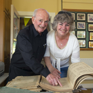 Fr Mernagh and past pupil Catherine Forristal looking at an old roll book at the 75th anniversary celebrations at Shanbogh NS