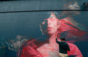 Artist Spear working on a mural during the 2019 Waterford Walls Festival