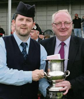Nigel O'Neill of the New Ross and District Pipe Band is presented with the 3rd place prize in Grade 3 by Victor Furness, Chairman of the Organising Committee.