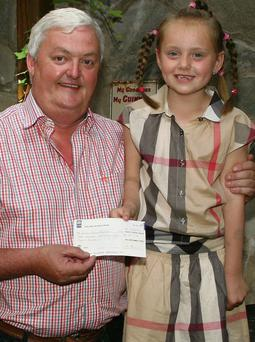 Young Ellie making a presentation of a cheque for €1,000 to Joe Ryan of the Gambia School Project in Prendergast's Pub, The Quay.