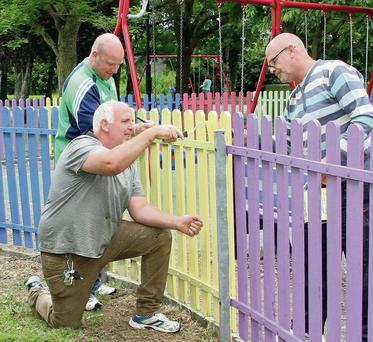 Cllr Anthony Connick with members of the Men's Shed, Stephen Roche (kneeling) and Jim McDonald, painting the fencing in the children's play area in the Town Park.